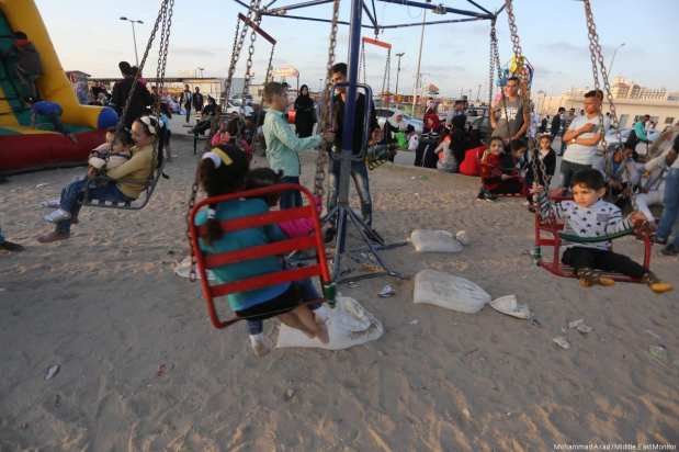Children play at the fair in Gaza as the electricity crisis forces families outdoors in the evenings and weekends. [Image: Mohammad Asad / Middle East Monitor]