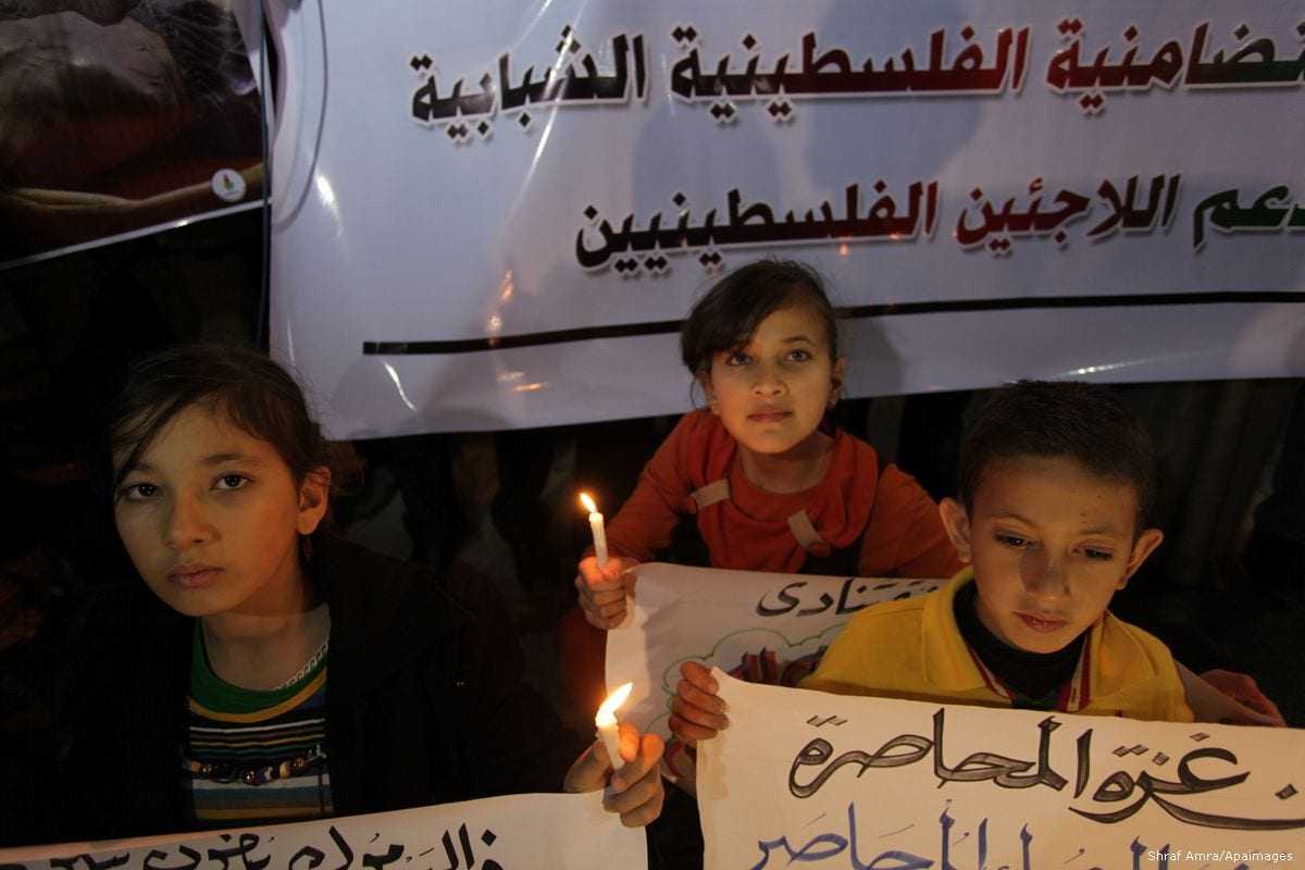 Image of Palestinian children holding banners in solidarity with Palestinian refugees in Syria [Ashraf Amra/Apaimages]
