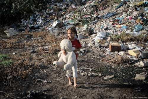 A Palestinian girl holds a stuffed toy near a sewage area in Gaza City on 17 September 2013 [Ezz Zanoun/Apaimages]