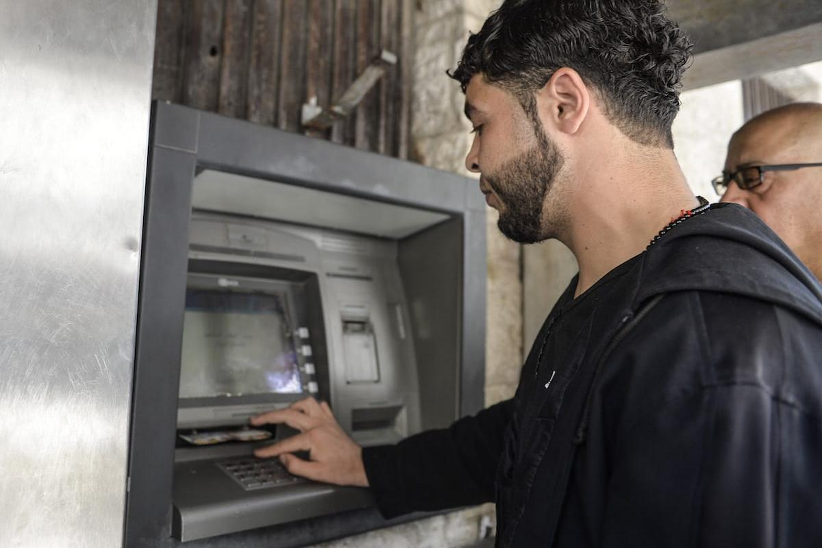 Palestinians wait in line to withdraw money from cash points on 10 May, 2017 [Mustafa Hassona/Anadolu Agency]