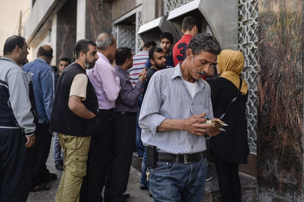 Palestinians, in Gaza City, wait in a queue to withdraw money from cash points after the decision of cutting the salaries by 30-percent was taken by the government officials on 10 May, 2017 [Mustafa Hassona/Anadolu Agency]