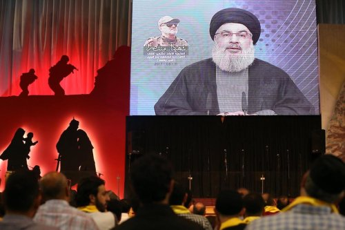 People shout slogans during a commemoration event for Mustafa Badreddine, a soldier of Hezbollah killed in Syria, as Secretary-General of Hezbollah Hassan Nasrallah live broadcasts in Dahieh district of Beirut, Lebanon on 11 May, 2017 [Ratib Al Safadi/Anadolu Agency]