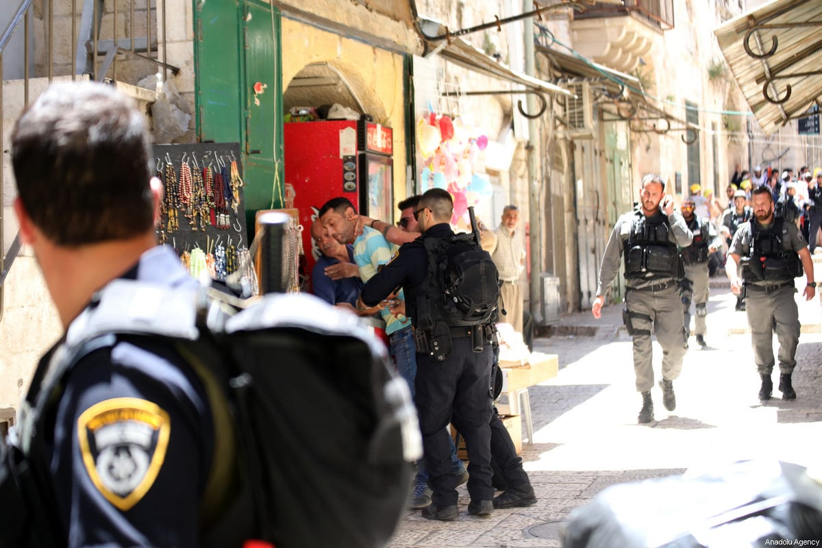 Israeli security forces take a Palestinian man into custody, who entered into the crime scene, as they inspect the crime scene after a Jordanian man was shot dead in an alleged stabbing attack in East Jerusalem, on 13 May, 2017 [Mostafa Alkharouf /Anadolu Agency]