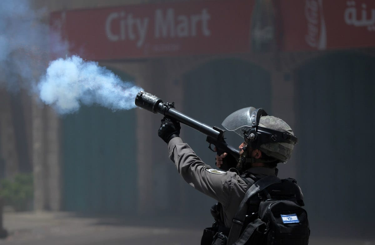 An Israeli soldier fires tear gas at Palestinians in the West Bank on 15 May 2017 [Mamoun Wazwaz/Anadolu Agency]
