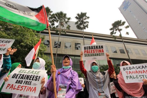 People hold placards as they gather during a demonstration in solidarity with Israeli held Palestinian prisoners in front of the Embassy of Israel building in Jakarta, Indonesia on 18 May, 2017 [Adem Şalvarcıoğlu/Anadolu Agency]