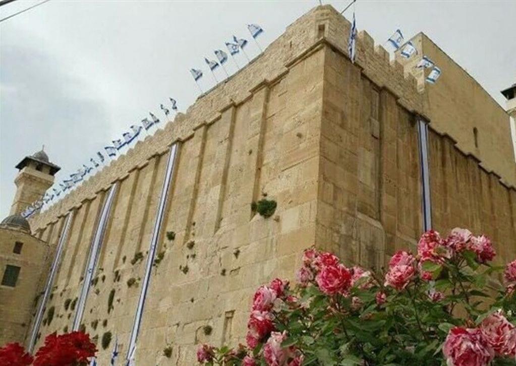 Settlers fly Israeli flag over Hebron's Ibrahimi Mosque on 2 April 2017 [Ma'an News]