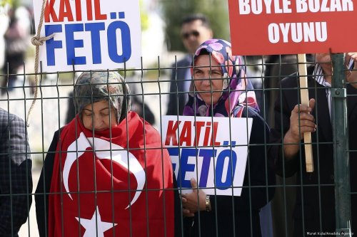 People hold banners during a protest against defendants involved in last July's attempted coup in Turkey in front of the prison where the defendants are being held on May 22, 2017 [Murat Kula/Anadolu Agency]