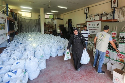 Palestinian take their aid bags as The Freedoms And Humanitarian Relief (IHH) gives food aid in Gaza City, Gaza on 25 May, 2017 [Mustafa Hassona/Anadolu Agency]
