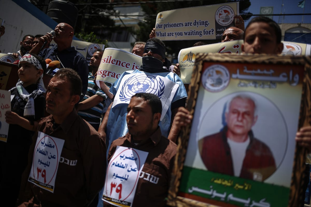 Palestinian demonstrators hold placards during a demonstration in support Palestinian prisoners held in Israeli jails in Gaza City, Gaza on May 25, 2017 [Ali Jadallah/Anadolu Agency]