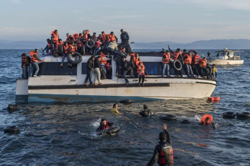 "Syrian and Iraqi refugees arrive from Turkey to Skala Sykamias, Lesbos island, Greece on 30 October 2015. Spanish volunteers (life rescue team - with yellow-red clothes) from ""Proactiva open arms"" help the refugees [Ggia / Wikipedia]"