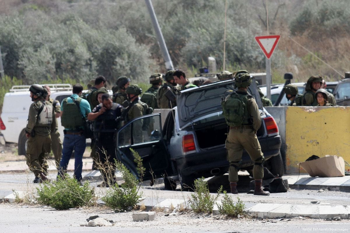 Image of Israeli soldiers surrounding a Palestinian driver and his vehicle [Nedal Eshtayah/Apaimages]