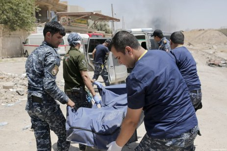 A dead body, left in a street, is being placed inside of a body bag by Iraqi army members in Mosul, Iraq on June 12, 2017 [Yunus Keleş / Anadolu Agency]