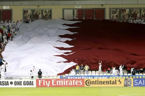 Fans raise the Qatari flag during the 2018 FIFA World Cup Asian Qualifying group A football match between Qatar and South Korea at the Jassim Bin Hamad stadium in Doha, Qatar on 13 June, 2017 [Mohamed Farag/Anadolu Agency]