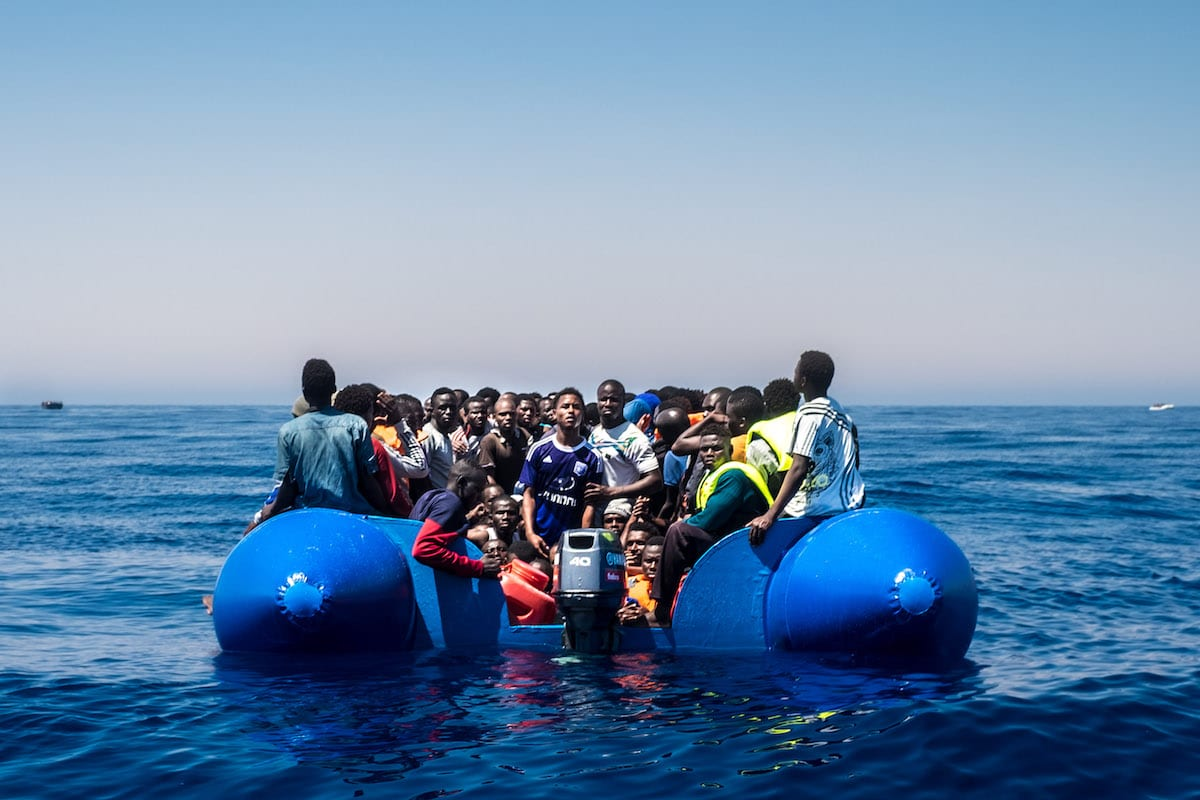 Refugees wait to get on onboard the rescue vessel Golfo Azzurro by members of the Spanish NGO Proactiva Open Arms, after being rescued from a wooden boat sailing out of control in the Mediterranean Sea near Libya on Thursday, June 15, 2017 [Marcus Drinkwater / Anadolu Agency]