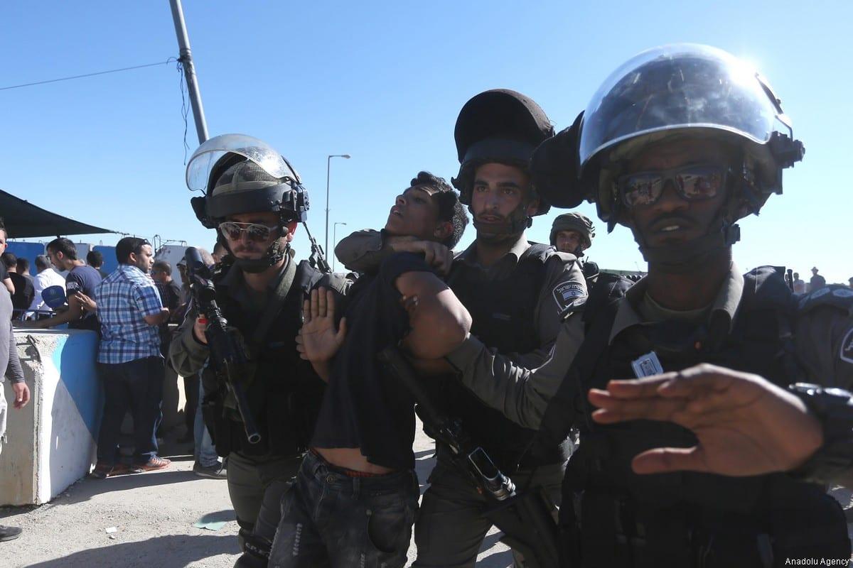 Israeli forces arrest a Palestinian boy on June 16, 2017 [Issam Rimawi/Anadolu Agency]