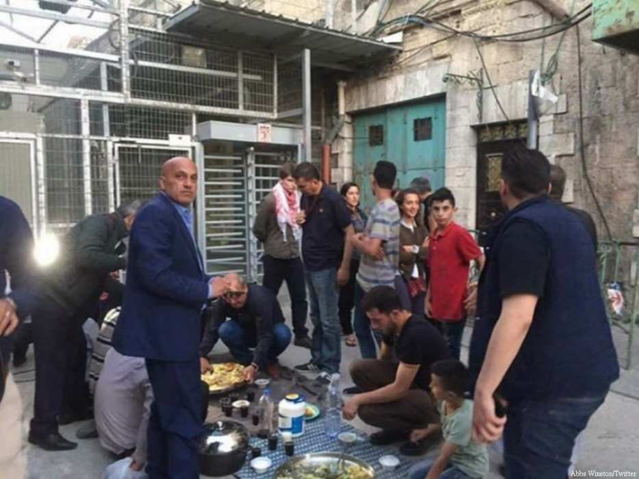 Palestinians break Ramadan fast at the Shuhada Street checkpoint in Hebron after Israeli Occupiers refused to let them through to go home on 5 June, 2017 [Abbs Winston‏/Twitter]