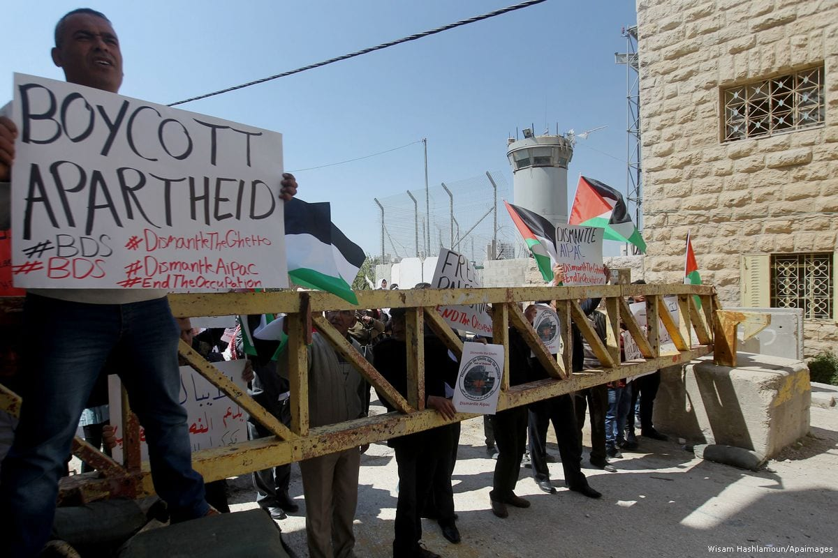 Palestinian demonstrators hold Palestinian flags and placards during a protest against illegal settlements in the West Bank on 26 March 2017 [Wisam Hashlamoun/Apaimages]
