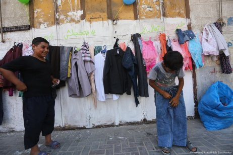 """Happy shoppers. The 'Wall of Blessings' has been decorated with the words """"Don't be shy"""", and """"Come get dressed"""" in the Gaza Strip on 23 June 2017 [Mohammed Asad/Middle East Monitor]"""