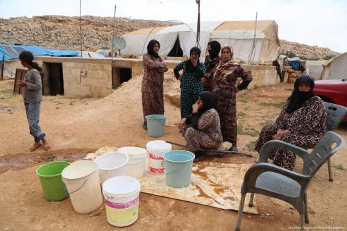 Syrian women living in a refugee camp, fill their buckets with water in Idlib, Syria on 23 June 2017 [İsmihan Özgüven/Anadolu Agency]