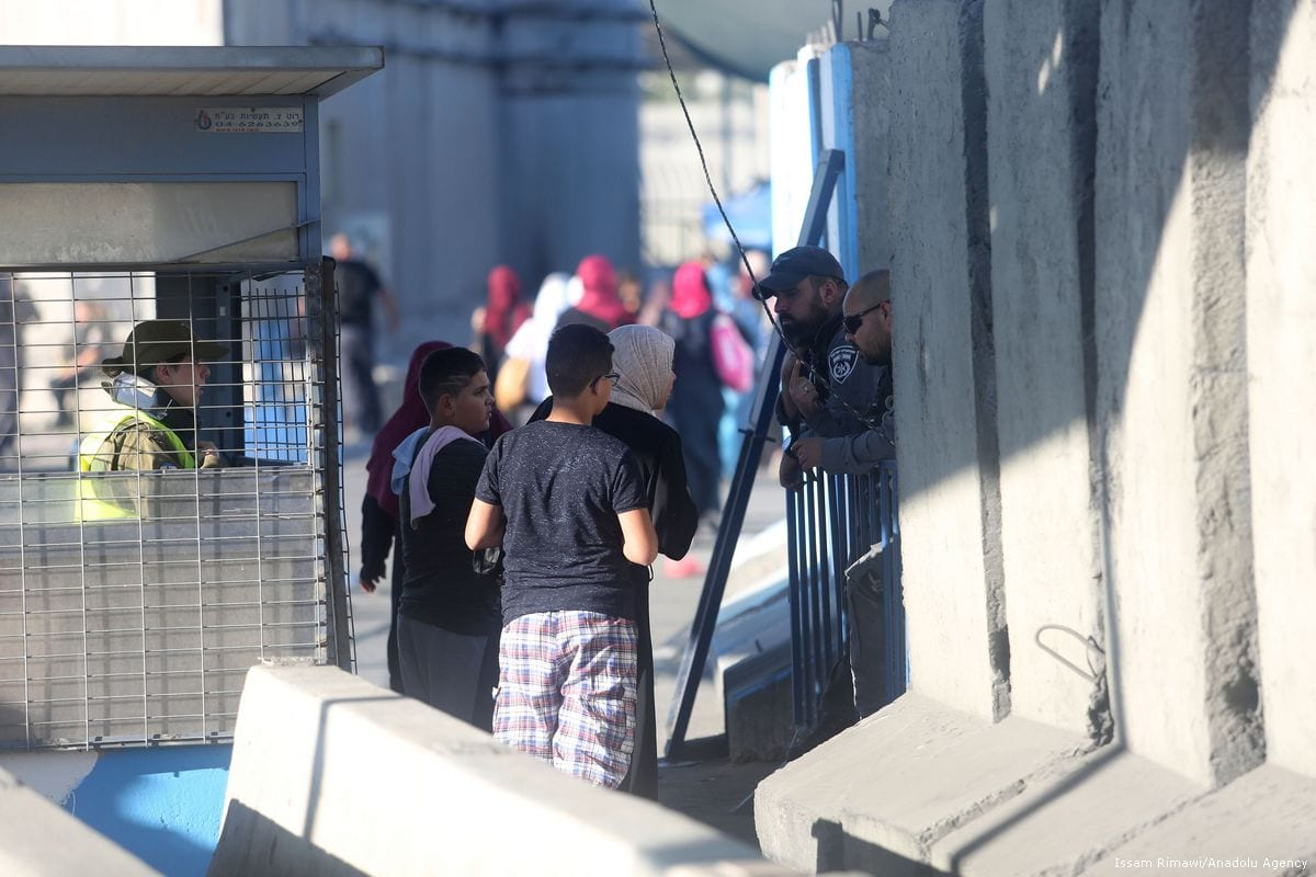 Palestinian worshippers line up to pass through the Qalandiya checkpoint from Ramallah into Jerusalem on 23 June 2017 [Issam Rimawi/Anadolu Agency]