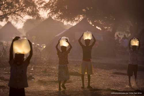 Children collect water for their families at sunset. Oxfam is currently producing over 300,000 litres of clean water a day for a population of around 80,000 displaced people who have settled in Awerial county, South Sudan. Clean water for drinking and cooking significantly reduces the risk of deadly water-borne diseases like cholera. [Image: commons.wikimedia.org | Oxfam East Africa ]