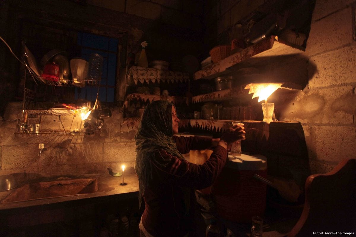A Palestinian women is seen using candles in her kitchen due to electricity shortage in Gaza on 8 July 2015 [Ashraf Amra/Apaimages]