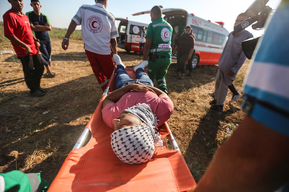 Medics tend to a Palestinian protester after he was wounded by Israeli security forces in Gaza City, Gaza on July 2 2017 [Mustafa Hassona/Anadolu Agency]