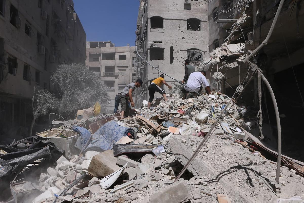Syrian search and rescue team workers inspect damaged buildings after the Assad Regime bombed residential areas in Damascus, Syria on 13 July 2017 [Ala Muhammed/Anadolu Agency]