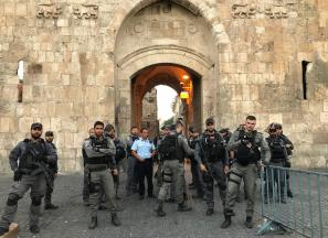 Security forces stand guard as Palestinians stage a protest in front of the new security metal detectors, outside one of the main entrances to the Al-Aqsa mosque in Jerusalem on 17 July, 2017 [Turgut Alp Boyraz/Anadolu Agency]