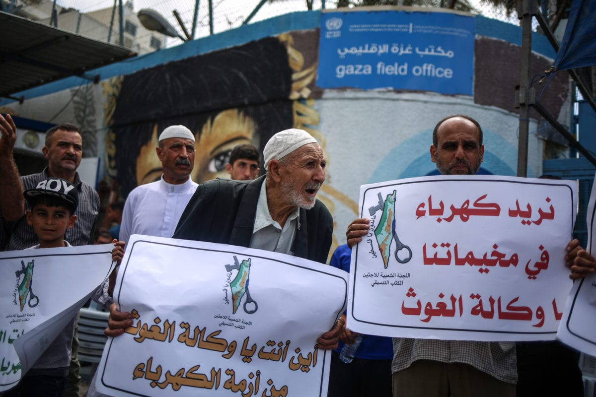 Demonstrators gather to protest electricity crisis in Gaza, organized by People's Committees, as they hold placards in front of The United Nations Relief and Works Agency for Palestine Refugees (UNRWA) headquarters in Gaza City, Gaza on July 19, 2017. [Ali Jadallah - Anadolu Agency]