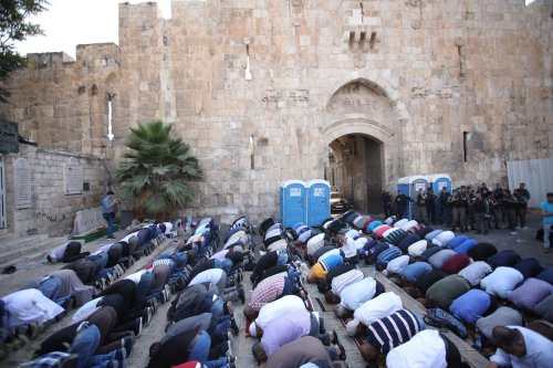 Palestinian worshippers perform the afternoon prayer outside the Al-Aqsa Mosque compound as they protest the detectors installed by Israel on 20 July 2017 [Mostafa Alkharouf/Anadolu Agency]