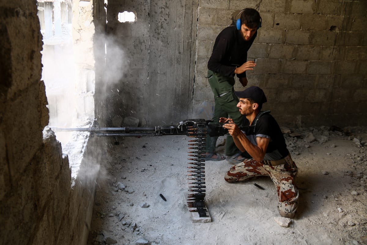 A member of opposition forces fires from a building during a clash after Assad Regime's forces hit a de-conflict zone, Ayn Tarma town, in the Eastern Ghouta region of Damascus, Syria on 24 July, 2017 [Ammar El Bushy/Anadolu Agency]