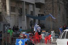 Settlers gather in front of a house in occupied Hebron, West Bank on 26 July 2017. The Palestinian Abu Rajab family had been evicted from the property which is legally theirs after over 100 settlers stormed it under the protection of occupation forces. [Mamoun Wazwaz /Anadolu Agency]