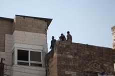 Settlers are seen on a rooftop in Hebron, West Bank on 26 July 2017. The Palestinian Abu Rajab family were evicted from their house, which is located in Old Town region, by Israeli occupiers accompanied with Israeli forces, claiming that they are the owners of the house. [Mamoun Wazwaz /Anadolu Agency]