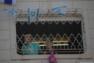Settlers erect Israeli flags at the windows and roof of a Palestinian house on 26 July 2017 after they took it over and evicted the family living in it the day earlier in the occupied West Bank city of Hebron. [Mamoun Wazwaz /Anadolu Agency]