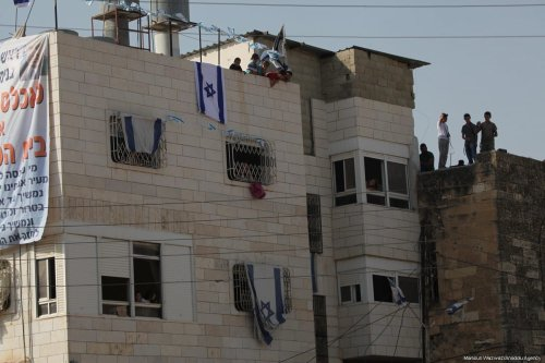 A Palestinian house is seen with an Israeli flag on it as settlers take over and evict the legal residents in Hebron, West Bank on 26 July, 2017 [Mamoun Wazwaz/Anadolu Agency]