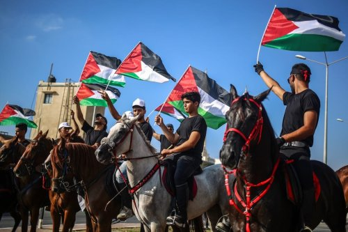 Palestinians ride horses as they hold Palestinian flags during a demonstration to show solidarity with Jerusalem and Al-Aqsa Mosque in Gaza City, Gaza on 2 August 2017 [Ali Jadallah/Anadolu Agency]
