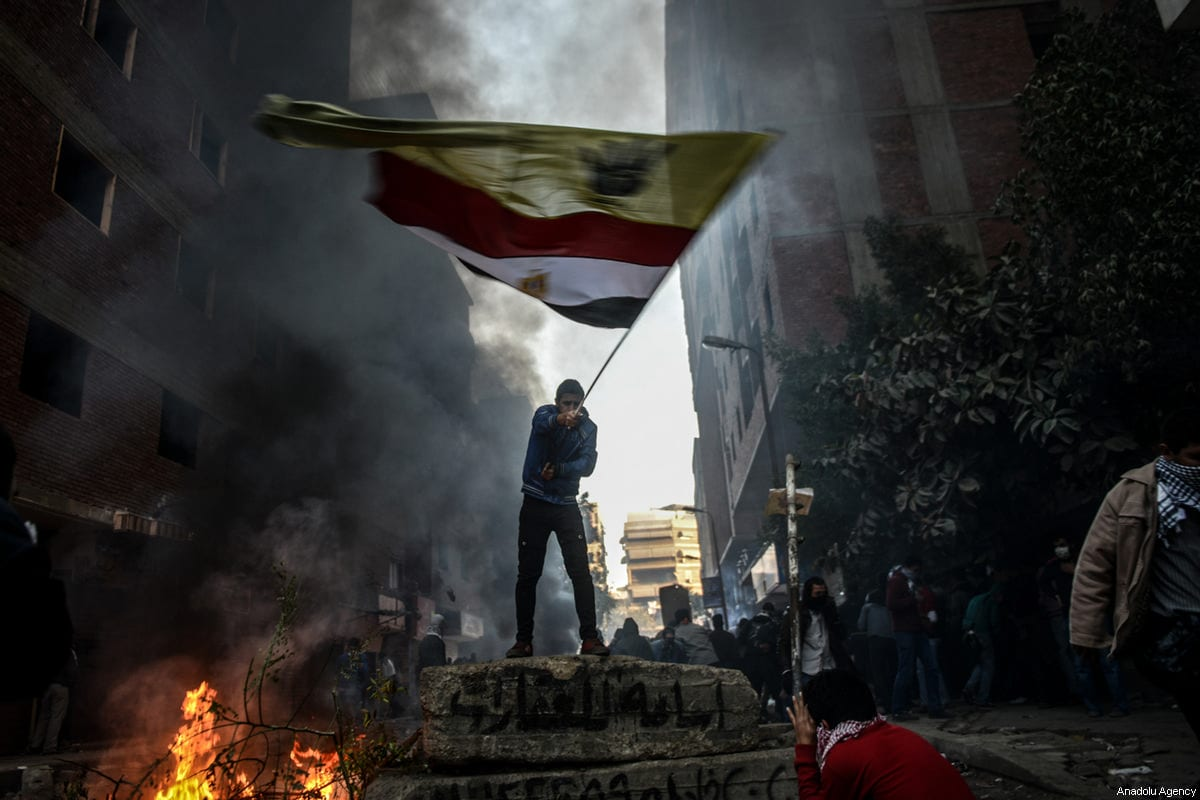 A file photo dated December 27, 2013 shows a protester waving the Egyptian and Rab'aa Al Adawiya flags during clashes between police and anti-military protesters in Cairo, Egypt [Mohammed Elshamy / Anadolu Agency]