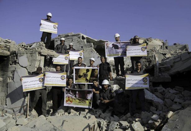 Men, members of Syrian civil defense organisation, White Helmets release a white pigeon for people who lost his life in chemical attack that in the Eastern Ghouta region of Damascus, Syria on 22 August, 2017 [Amer Almohibany/Anadolu Agency]