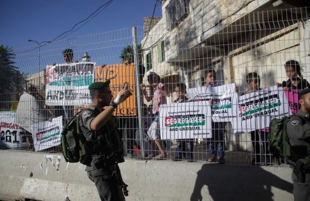 Palestinians hold banners during a protest against Israeli restrictions in Hebron, West Bank on 28 August 2017 [Mamoun Wazwaz/Anadolu Agency]