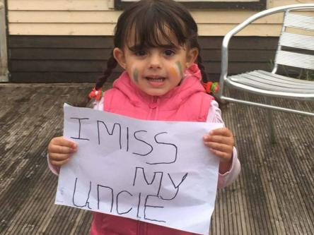 Ibrahim Halawa's niece holds out a poster for her uncle, who has been imprisoned since 2013. [click to enlarge]