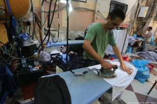 Gaza's tailors are working hard towards making school uniforms for the new academic year. [Image: Mohammad Asad / Middle East Monitor]