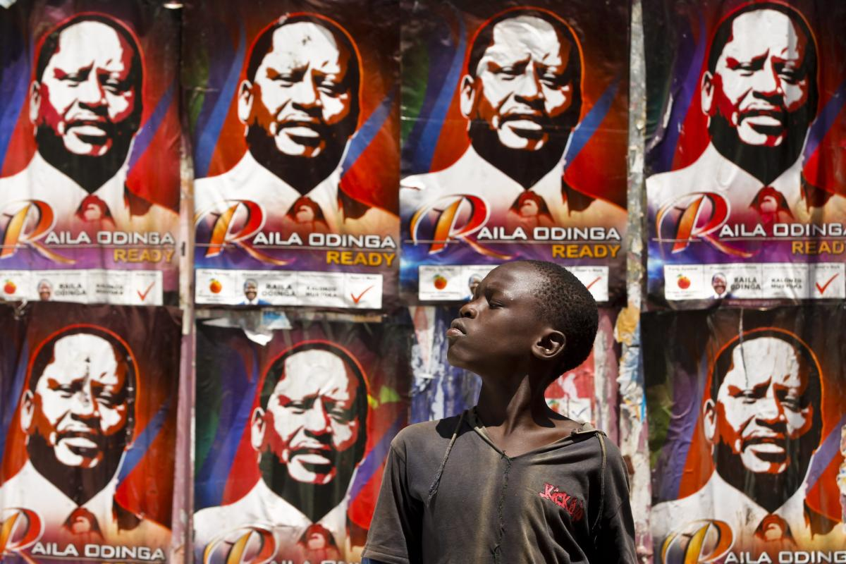 A young Kenyan boy looks on in front of the prime minister Raila Odinga's campaign posters on the wall near a polling station in the Kibera slum, Nairobi, Kenya, 04 March 2013 [EPA/Dai Kurokawa]