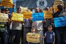 "Palestinian Ministry of Agriculture employees hold banners during a demonstration against Palestinian Government's ""obligatory and early retirement of employees"" decision in front of the Palestinian Cabinet building in Gaza, West Bank on 12 September, 2017 [Ali Jadallah/Anadolu Agency]"
