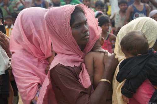 A Rohingya Muslim woman, fled from ongoing military operations in Myanmar's Rakhine state, holds a child at a refugee camp in Cox's Bazar, Bangladesh on September 20, 2017 [Safvan Allahverdi / Anadolu Agency]