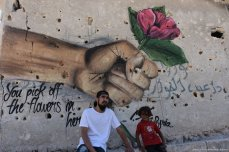 A damaged wall with bullet holes is decorated with an anti-war mural by a Turkish graffiti artist in Aleppo, Syria on 26 September 2017 [Halit Süleyman/Anadolu Agency]
