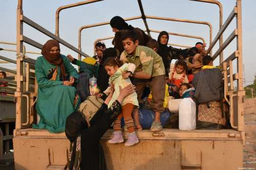 Iraqi women with children, who fled from Havice district due to the ongoing operations held by Iraqi army and Peshmerga against Daesh, arrive to take shelter in Peshmerga controlled Dibis district of Kirkuk, Iraq on 30 September 2017 [Ali Mukarrem Garip/Anadolu Agency]