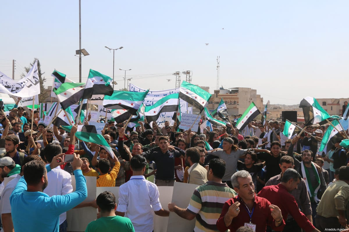 Syrians gather to support Turkish soldiers' deployment on Idlib border as they hold Turkish and Syrian flags in Idlib, Syria on October 14, 2017. Syrian demonstrators also call for a day of anger to protest Assad regime forces' crimes over the country [Abdurrazzak Şekirdy / Anadolu Agency]