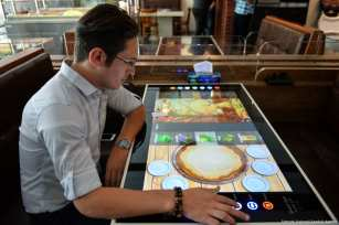 A man selects his food served by robot waiter, which moves on rail system placed between tables. All services including payment, placing an order, are provided automatically via tables, which turn to digital screens like an tablet computer, at 'RoboChef' [Fatemeh Bahrami/Anadolu Agency]