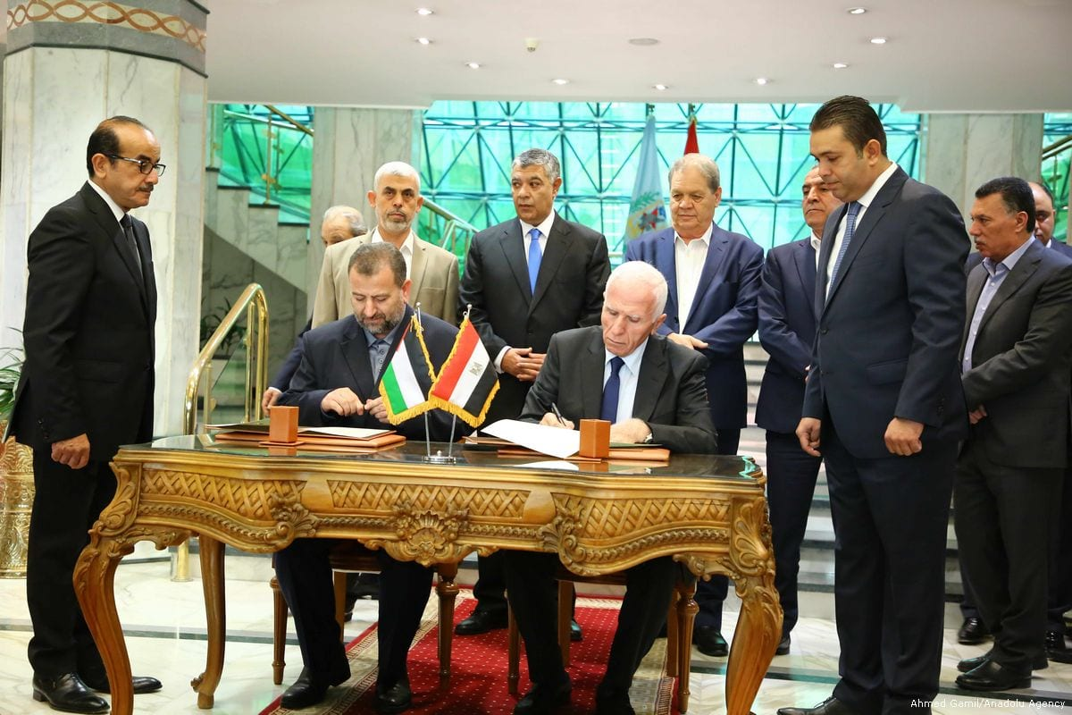 Fatah Commissioner of National Affairs and Fatah Central Committee member Azzam Al-Ahmad (2nd R) and Hamas Political Bureau member Saleh Aruri (2nd L) sign an agreement on building a consensus in Cairo, Egypt on 12 October, 2017 [Ahmed Gamil/Anadolu Agency]